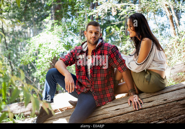 Young couple sitting on tree in forest - Stock-Bilder