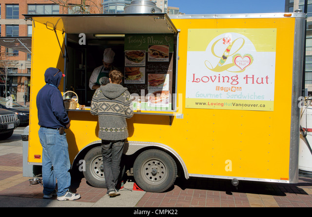 People being served at a vegan street food wagon in Yaletown, Vancouver, British Columbia, Canada. - Stock Image