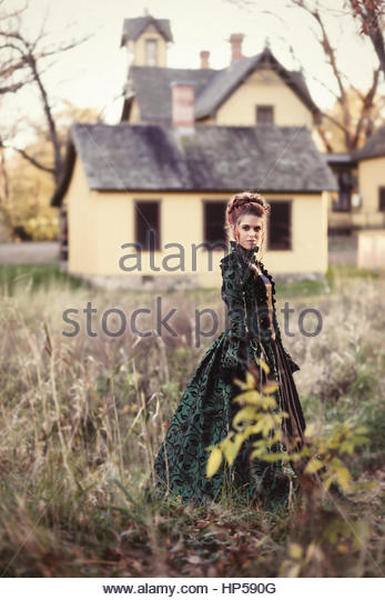 Victorian young woman standing in front of Victorian home - Stock Image