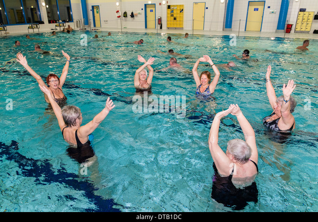 A group of women practices water gymnastics in a pool. - Stock Image