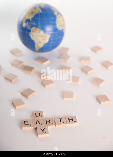 Concept: 'Earth Day' spelled out in Scrabble letters with out of focus globe in background. Isolated on - Stock Image