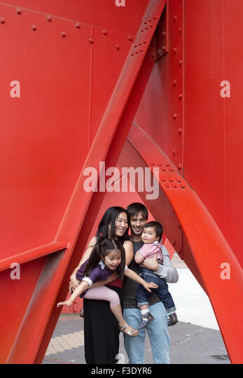 Family with two children standing beneath sculpture - Stock Image