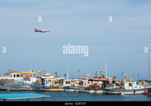 Airliner on approach to Larnaca International Airport over Larnaca fishing port. - Stock Image