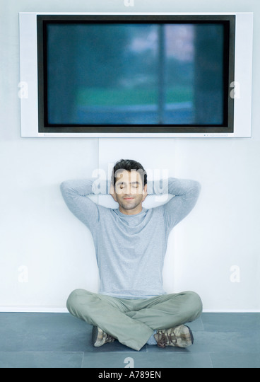 Man sitting on floor under wide screen TV, hands behind head and eyes closed - Stock Image
