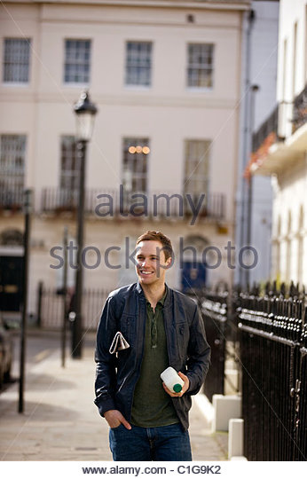A young man carrying a newspaper and a pint of milk - Stock Image