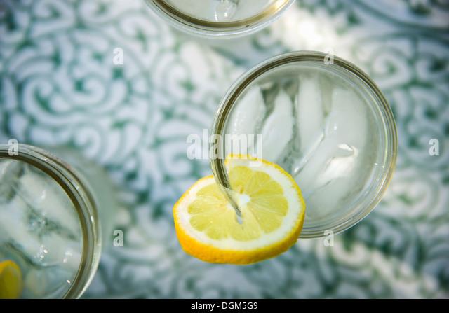 Making lemonade Overhead shot of lemonade glasses fresh slice of lemon in edge of glass Organic lemonade drinks - Stock Image