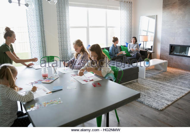 Girls enjoying play date painting at dining room table with mothers in background - Stock Image