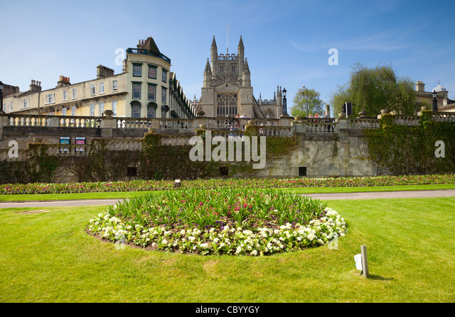 Formal flower bed in Parade Gardens, with Bath Abbey and The Orangerie, on a beautiful spring day. - Stock Image