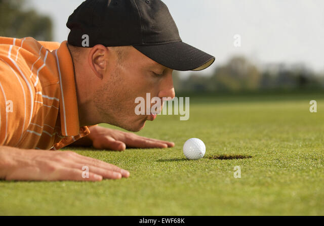 Close-up of man blowing on golf ball - Stock Image