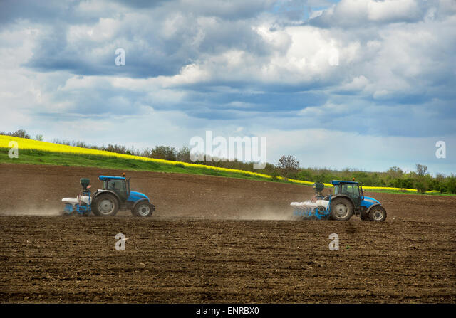 Farming a field with a tractors - Stock Image