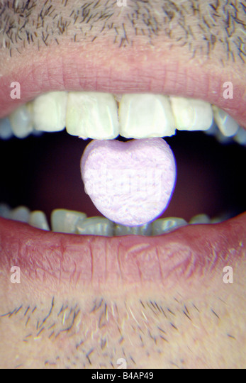 Closeup Portrait of a Scruffy Man Holding a Valentines Love Candy Heart in His Teeth Copy Space - Stock Image