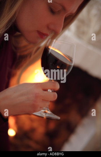 Young woman tasting glass of red wine by the fireplace, side view - Stock Image
