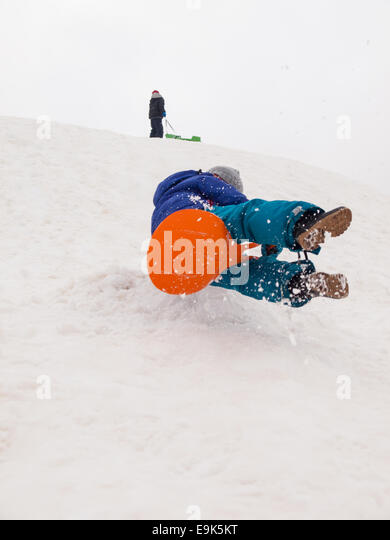 small boy sledging fast down a steep hill with child standing at top of hill in background - Stock Image