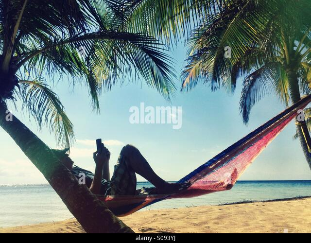 Man trading electronic book under a palm tree, Belize - Stock Image