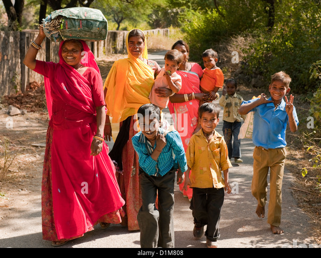 A happy smiling colorful Indian family group of women boys girls and a baby return from shopping on a quiet road - Stock-Bilder