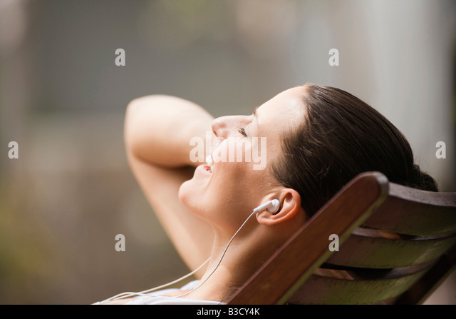 Young woman in deck chair listening to MP3-Player, portrait - Stock Image
