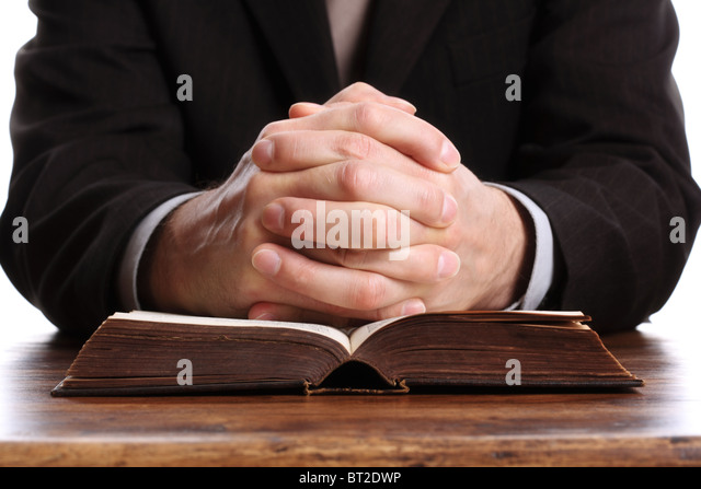 Praying hands on an open bible - Stock Image