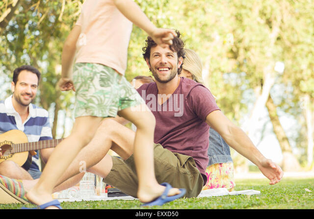 Man at picnic watching children play - Stock Image