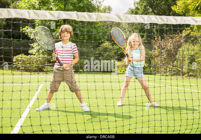 Children playing tennis on grass court - Stock Image