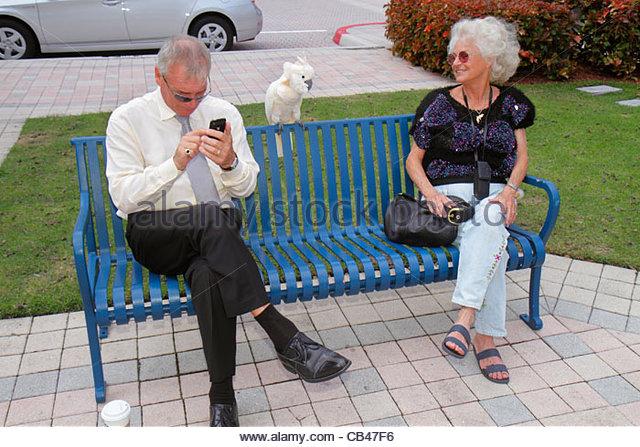 Boca Raton Florida Mizner Park Plaza Real man woman senior bench cockatoo parrot checking mobile cell smart phone - Stock Image