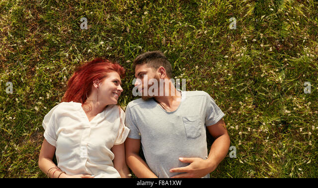 Overhead view of happy young couple in love relaxing on the grass. Affectionate young man and woman lying on grass - Stock-Bilder