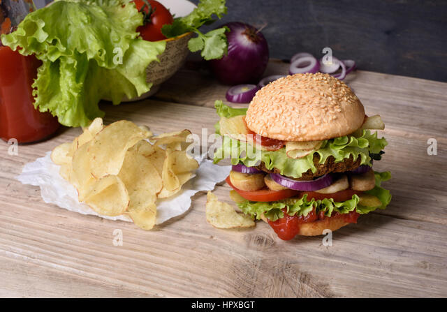 Juicy cheeseburger on wooden table with potato chips and ketchup. - Stock Image