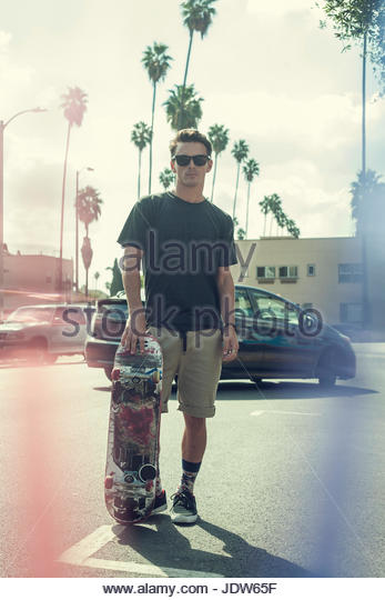 Portrait of young man with skateboard - Stock-Bilder