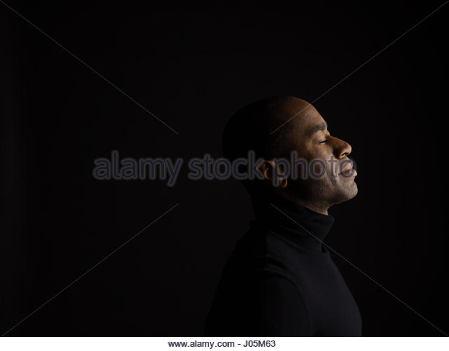 Profile portrait serene African American man with eyes closed and head back against black background - Stock Image