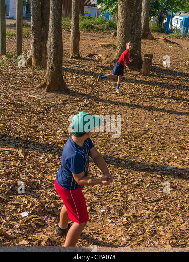 Two Cuban boys play stick ball baseball with a stick for a bat and a prescription bottle for a ball in western Cuba. - Stock Image