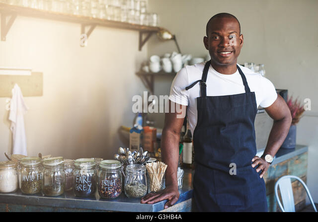 Handsome black entrepreneur stands by cafe counter lined with jars of tea while wearing dark colored apron - Stock Image