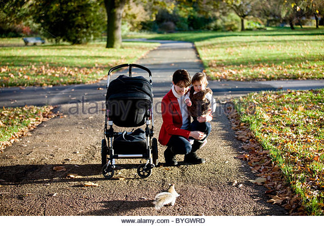 A mother holding her baby girl in the park, looking at a squirrel - Stock Image