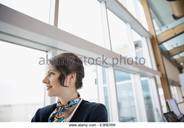 Flight attendance looking out airport window - Stock Image