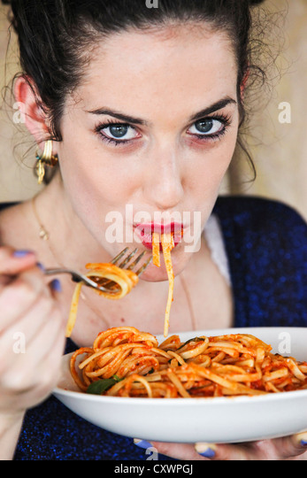 Woman eating plate of pasta - Stock Image