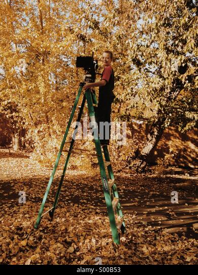 Boy on ladder with movie camera - Stock Image
