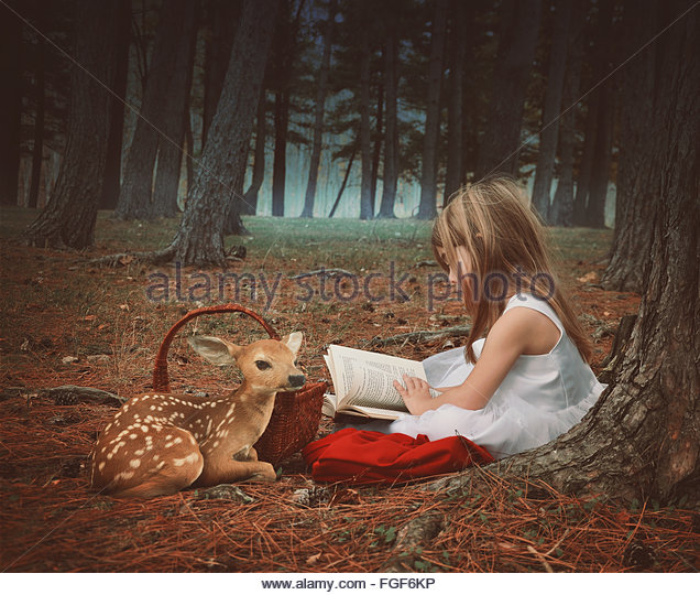 A little girl in a white dress is reading on old story book with a baby deer in the dark woods for an education - Stock Image
