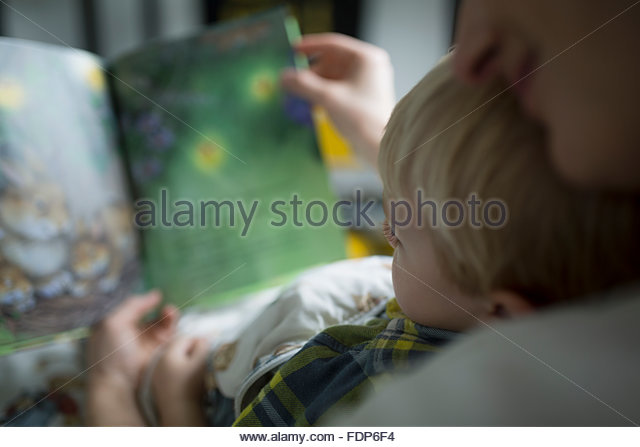 Close up mother and son reading book - Stock Image