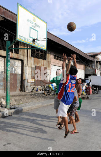 Boys playing basketball on a street in Cebu, Philippines, Southeast Asia, Asia - Stock Image