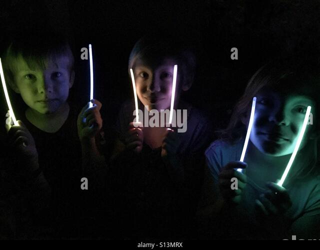 Three children light their faces with glow sticks in the dark. - Stock Image