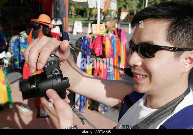 Sint Maarten Philipsburg Dutch duty free shopping souvenirs Asian male digital camera - Stock Image
