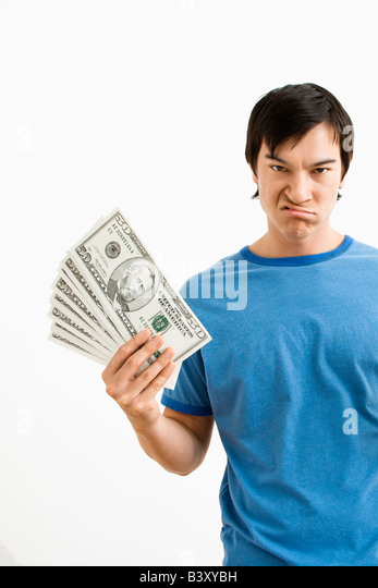 Asian young man holding money with disgust on his face - Stock Image