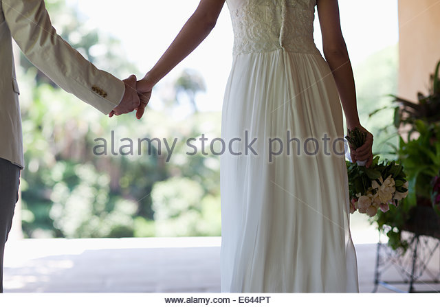 Bride and groom holding hands - Stock Image