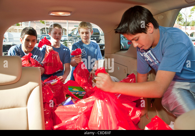 Multi ethnic Teen boys from Lion's Heart organization collecting donations for food bank. Good deeds Editorial - Stock Image