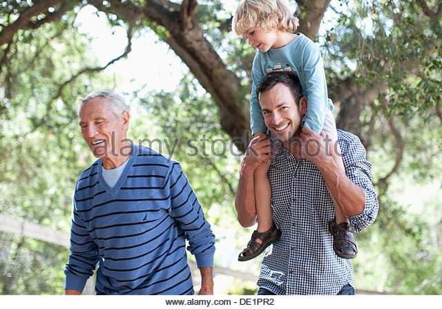 Three generations of men walking outdoors - Stock Image