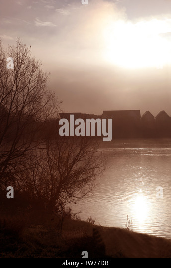 Outline of houses in the distance next to a misty lake - Stock Image