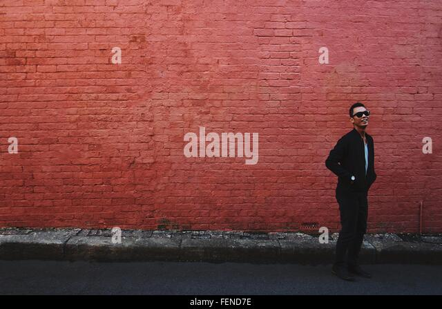 Smiling Young Man In Sunglasses Standing On Footpath - Stock Image
