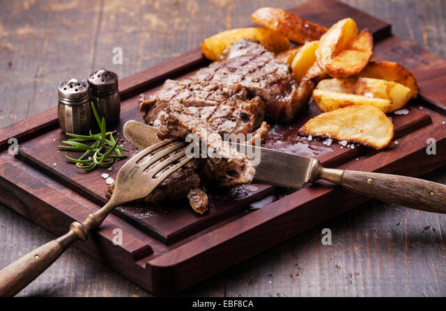 Sliced well done grilled New York steak with roasted potato wedges on cutting board on dark wooden background - Stock Image