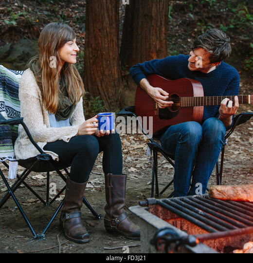 A young couple sits near the campfire enjoying music and nature in Big Sur, California. - Stock Image