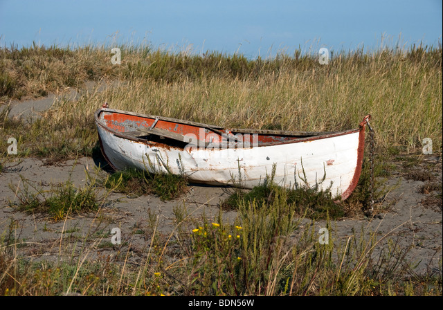abandoned old double ended rusting metal row boat beached on a grassy dune in Fort Worden State Park Port Townsend - Stock Image