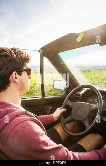 Young man leaning driving convertible - Stock Image
