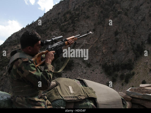 An Afghan National Army (ANA) soldier with the 201st ANA Corps aims a sniper rifle while standing watch outside - Stock Image